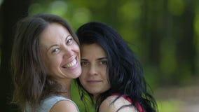 Deux amis féminins étreignant près de l'un l'autre souriant, amitié de mouvement lent banque de vidéos