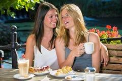 Deux amis féminins étroits en café extérieur Photographie stock