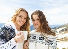 Deux amis féminins appréciant la boisson chaude en café à la station de sports d'hiver Photos libres de droits