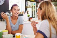 Deux amis féminins appréciant le petit déjeuner à la maison ensemble Photo stock