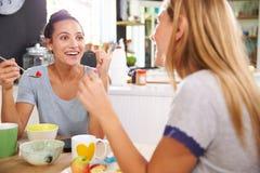 Deux amis féminins appréciant le petit déjeuner à la maison ensemble Photographie stock