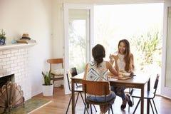 Deux amis féminins appréciant le repas à la maison ensemble Photos stock