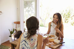 Deux amis féminins appréciant le repas à la maison ensemble Photo stock