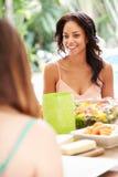 Deux amis féminins appréciant le repas dehors à la maison Photographie stock libre de droits