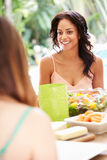 Deux amis féminins appréciant le repas dehors à la maison Photo stock