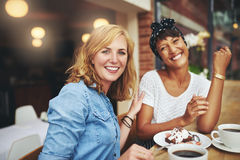 Deux amis féminins attirants appréciant le café Photo stock