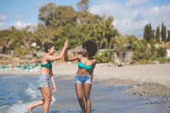 Deux amis féminins au bord de la mer se donnant la haute cinq Photographie stock