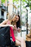 Deux amis féminins avec des bagages utilisant le navigateur Photos libres de droits