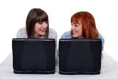 Deux amis féminins avec des ordinateurs portatifs. Images libres de droits