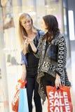 Deux amis féminins avec des sacs dans le centre commercial Image stock