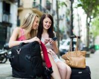 Deux amis féminins avec le bagage utilisant la carte Photographie stock libre de droits