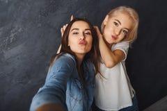 Deux amis féminins ayant l'amusement au fond de studio image stock