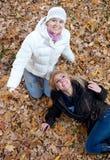 Deux amis féminins ayant l'amusement dans le stationnement d'automne Images stock
