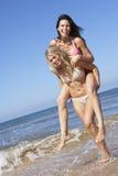 Deux amis féminins ayant l'amusement des vacances de plage ensemble Images libres de droits