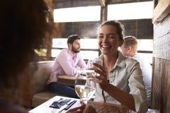 Deux amis féminins ayant une boisson à une table dans une barre Image libre de droits