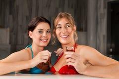 Deux amis féminins buvant du thé dans la piscine Photographie stock libre de droits