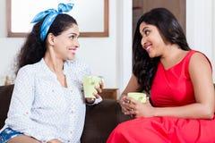 Deux amis féminins buvant du thé ou du café à l'intérieur Photos stock