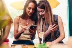 Deux amis féminins caucasiens de sourire observant des photos et des vidéos sur le smartphone se reposant dans le café ayant la p Image stock