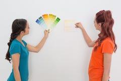 Deux amis féminins choisissant la couleur pour peindre une salle Image stock