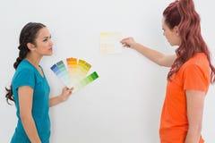 Deux amis féminins choisissant la couleur pour peindre une salle Images stock