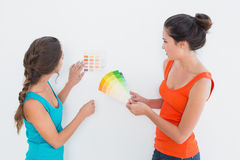 Deux amis féminins choisissant la couleur pour peindre une salle Photos stock