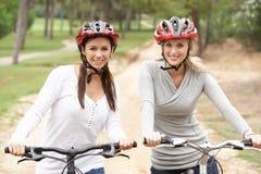 Deux amis féminins conduisant des vélos en stationnement Photo stock