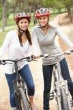 Deux amis féminins conduisant des vélos en stationnement Images libres de droits