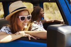 Deux amis féminins conduisant la voiture à couvercle serti sur la route de campagne Photo libre de droits