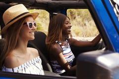 Deux amis féminins conduisant la voiture à couvercle serti sur la route de campagne Photo stock