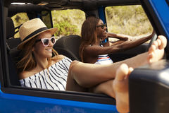 Deux amis féminins conduisant la voiture à couvercle serti sur la route de campagne Photographie stock libre de droits