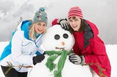 Deux amis féminins construisant le bonhomme de neige des vacances de ski Photos stock