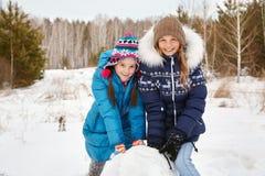 Deux amis féminins construisant un bonhomme de neige Images libres de droits
