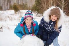 Deux amis féminins construisant un bonhomme de neige Photo stock
