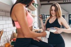 Deux amis féminins convenables prenant le petit déjeuner, se reposant après séance d'entraînement Image libre de droits