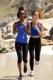 Deux amis féminins courant sur la plage Photographie stock