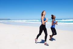 Deux amis féminins courant sur la plage Images libres de droits