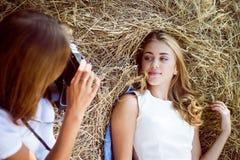 Deux amis féminins détendant dans le pays dégrossissent sur le foin Images stock