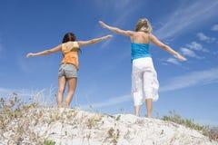 Deux amis féminins détendant sur la plage Photographie stock libre de droits