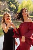 Deux amis féminins dansent heureusement dehors le long des rivages d'un lac photo libre de droits