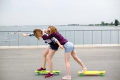 Deux amis féminins de sourire apprenant le longboard de monte avec s'aider Concept d'amitié images libres de droits