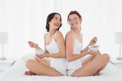 Deux amis féminins de sourire avec des cuvettes se reposant sur le lit Photo libre de droits