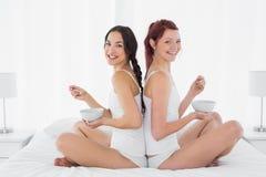 Deux amis féminins de sourire avec des cuvettes se reposant sur le lit Image stock