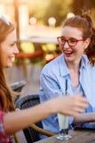 Deux amis féminins de sourire parlant, café potable dehors dans la ville Image stock