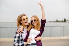 Deux amis féminins de sourire s'étreignant sur la rue Concept de vacances, de vacances, d'amour et d'amitié photographie stock libre de droits