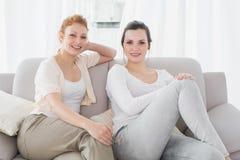 Deux amis féminins de sourire s'asseyant sur le sofa dans le salon Photo libre de droits