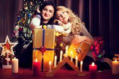 Deux amis féminins devant l'arbre de Noël Photos stock