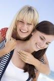 Deux amis féminins embrassant sur la plage Photos stock