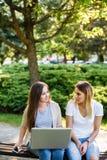 Deux amis féminins en parc fonctionnant quelque chose sur leur ordinateur portable Image libre de droits