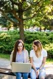Deux amis féminins en parc fonctionnant quelque chose sur leur ordinateur portable Photographie stock