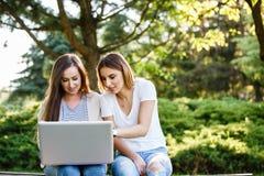 Deux amis féminins en parc se reposant sur le banc et travaillant au lapto Image stock